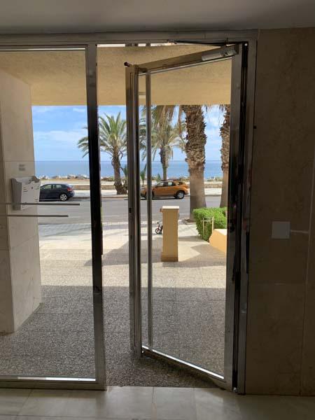 Puerta de portal en acero inoxidable con doble hoja simétrica desde el interior