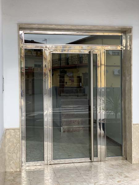 Puerta de portal en acero inoxidable con una hoja